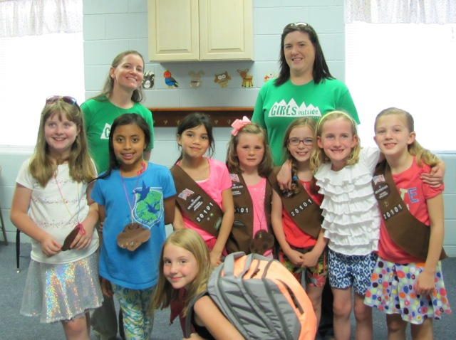 Brownie Troop 20101 poses with Girls Outside Guides Kelly Sturner (green shirt, left) and Amiee Smith (green shirt, right). showing off the hiking backpack they packed together!