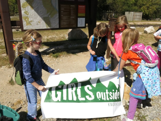 Hikers from one of our past hikes getting our banner ready for a pre-hike photo.